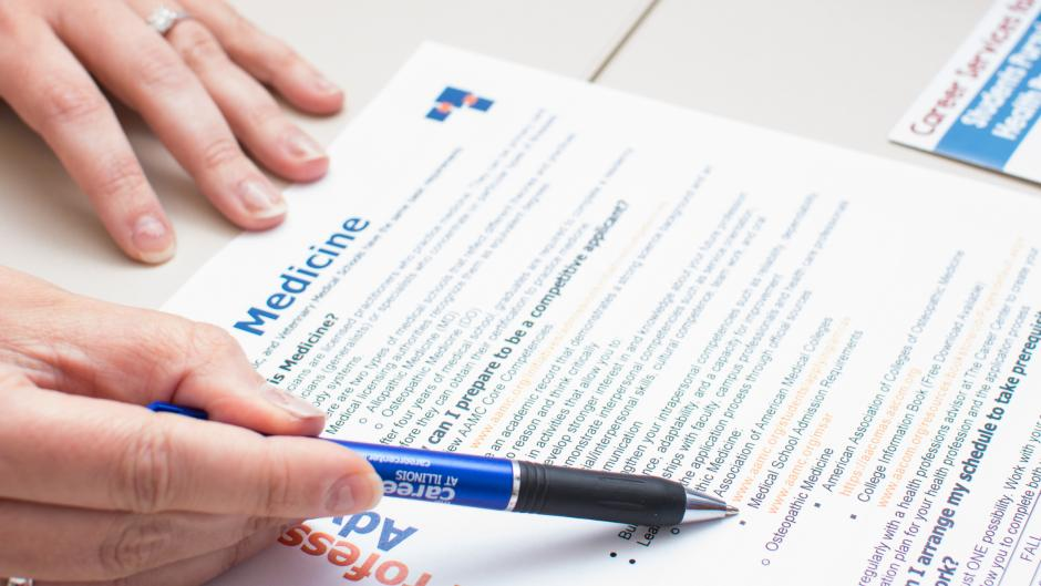 A hand uses a pen to point to elements on a handout about preparing for a career in medicine.