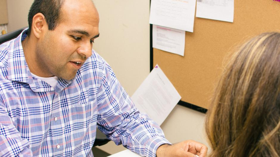 A career coach assists a student with her documents during an appointment.