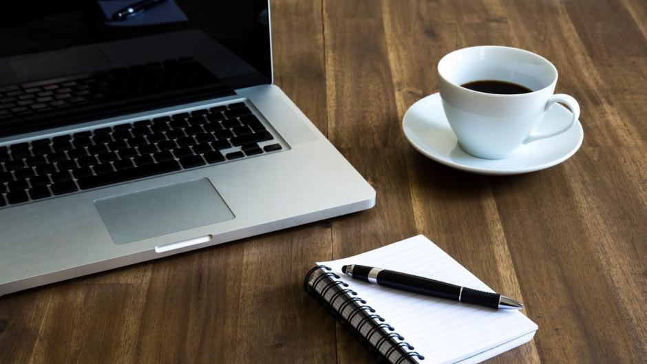 A laptop, a cup of coffee and a notebook with a pen placed on the table