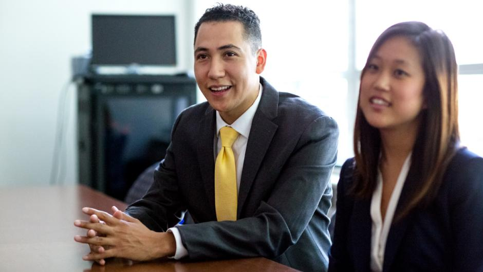 A male and female student dressed in professional attire attend a meeting around a conference table.