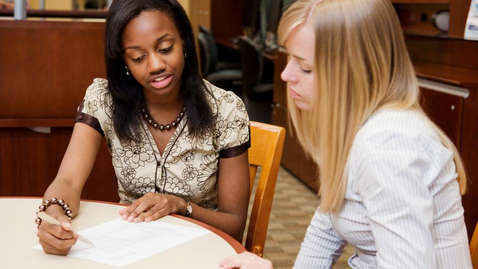 A career service paraprofessional points out helpful resume suggestions to a walk-in student.