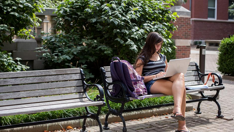 A female student takes a seat on a bench outside Harker Hall to work on her laptop.