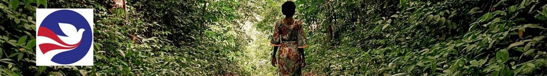 A woman in traditional garb walks through a forest in Liberia. The Peace Corp symbol appears to the left of the photo.