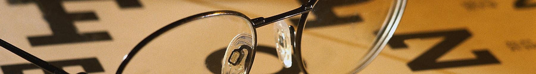 A pair of wire-frame glasses rests on an eye chart.