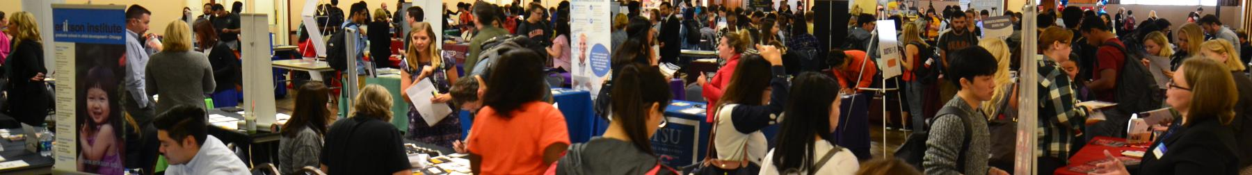 Students visit graduate and professional school booths during the graduate and professional school fair in the Illini Union.