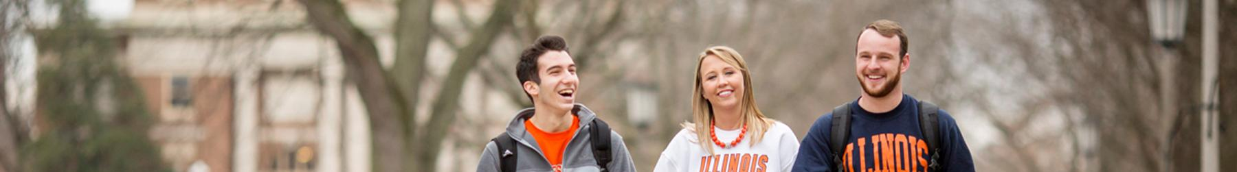 Three students sporting Illinois gear laugh together as they stroll side by side through the Main Quad.