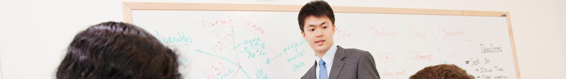A male student presents his research from a whiteboard in front of his classmates.