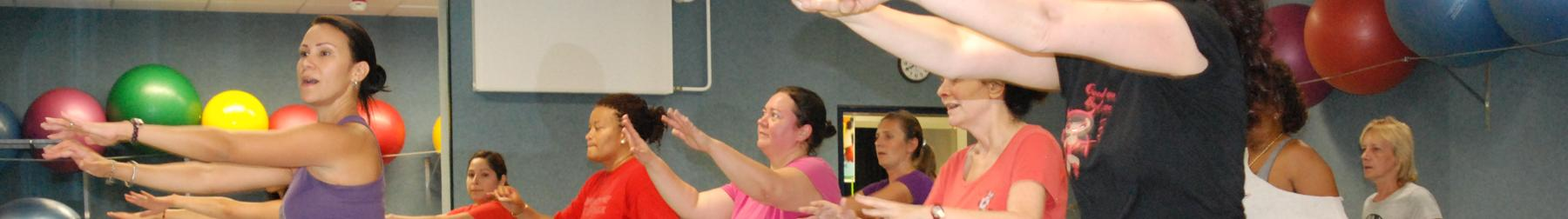 A fitness instructor leads a ca group of women in a zumba routine.