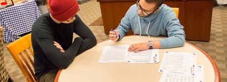A career service paraprofessional uses career center handouts to help a walk-in student with his cover letter.